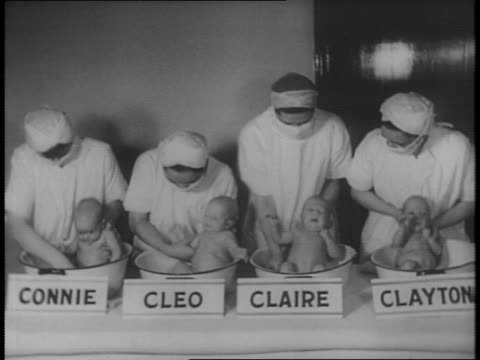 vídeos de stock, filmes e b-roll de four babies sit in tubs labeled connie cleo claire and clayton while four nurses attend to them wearing masks / panning shot over babies / babies are... - etiqueta mensagem