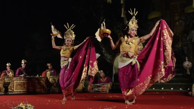 vidéos et rushes de ms four balinese girl dancer are performing tari penyambutan dance ( goddess of moon ) in puri saraswati temple audio / ubud, bali, indonesia, asia - coiffe traditionnelle