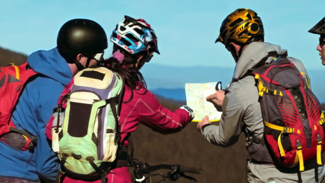 Four bikers deciding which route to take with bikes