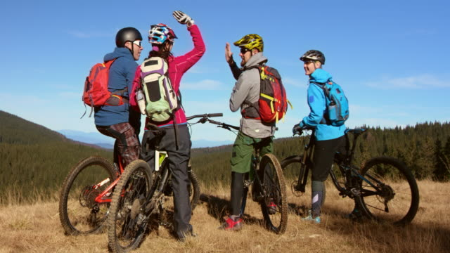 four bikers stopping on a clearing and doing high five - mountain bike stock videos & royalty-free footage