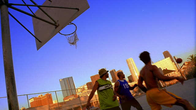 vídeos de stock, filmes e b-roll de canted four black men playing basketball on outdoor court / buildings in background / los angeles - lugar genérico
