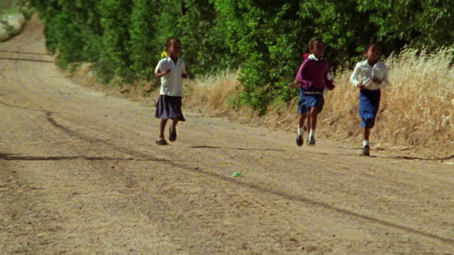 four black schoolgirls running along dirt road / south africa - 4人点の映像素材/bロール