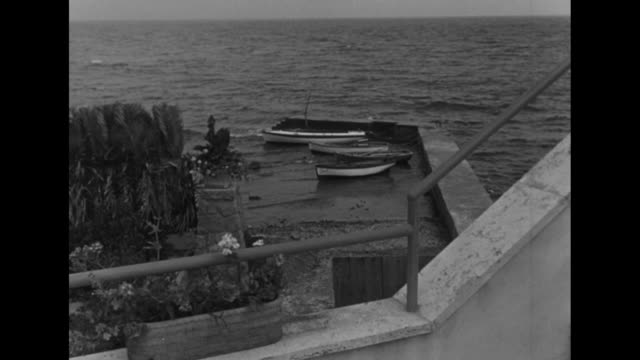 four boats tied up to jetty / wider shot from terrace of villa of boats tied up to jetty and sea beyond / shot of wall / shot from terrace of curving... - film director stock videos and b-roll footage