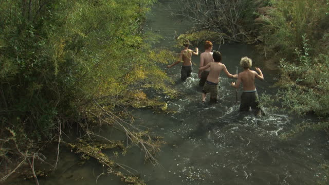 four boys hiking down a river - tyre swing stock videos & royalty-free footage
