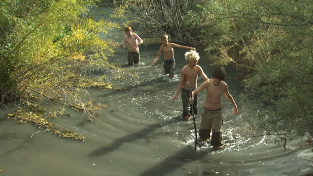 four boys hiking up a river - tyre swing stock videos & royalty-free footage