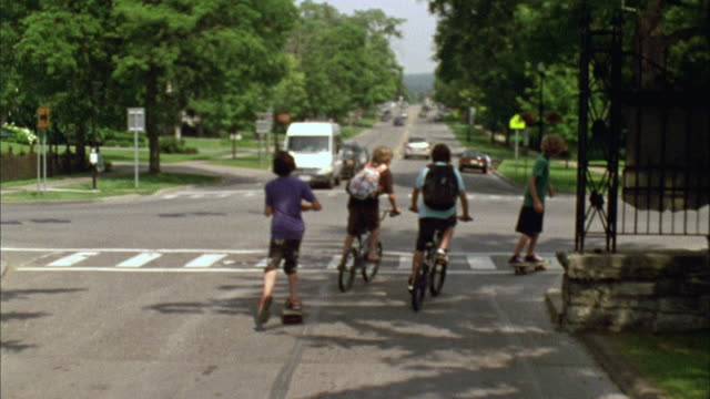 vidéos et rushes de ws ts pan four boys riding bikes and skateboarding down road, three turn corner and one continues straight on road / cazenovia, new york, usa - quartier résidentiel