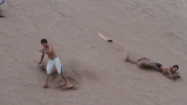 four boys sandboard down dune in necochea, argentina - 失敗点の映像素材/bロール