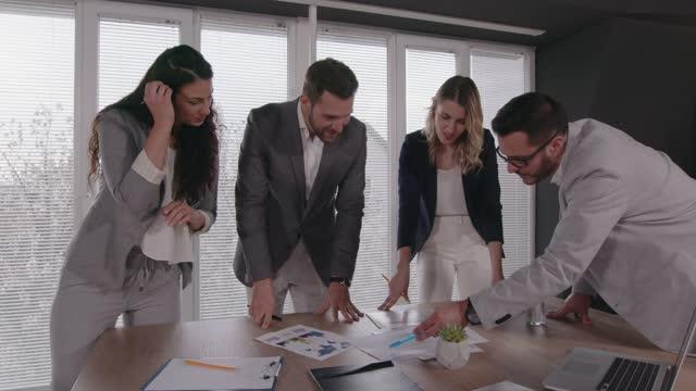quattro colleghi di lavoro che lavorano insieme a un progetto - abbigliamento da lavoro formale video stock e b–roll