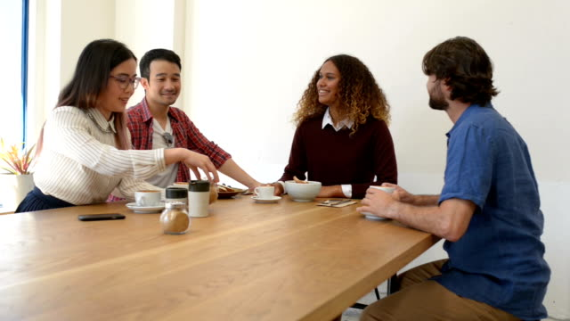 Four Business People in Discussion at Cafe