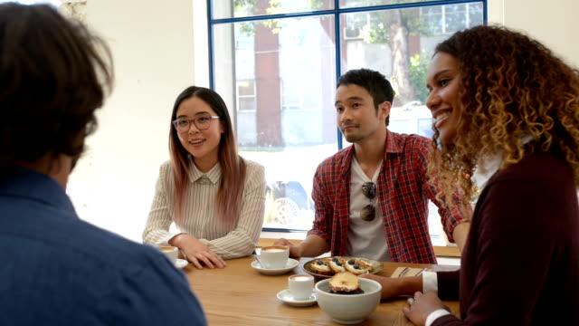 vídeos de stock e filmes b-roll de four business people in discussion at cafe - pão de fermento