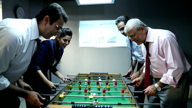 Four business people playing table football in the office, Delhi, India
