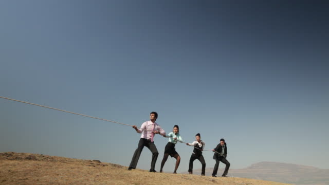 vidéos et rushes de four business people playing tug-of-war on the cliff of mountain - corde
