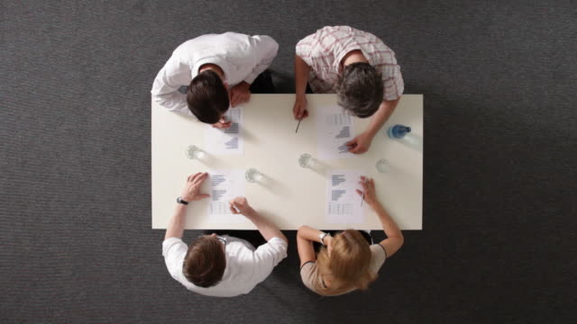 MS, four business people shaking hands after having a meeting, overhead view