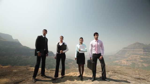 Four business people standing on the cliff of mountain