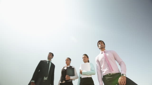 four business people standing on the cliff of mountain - dedication stock videos and b-roll footage
