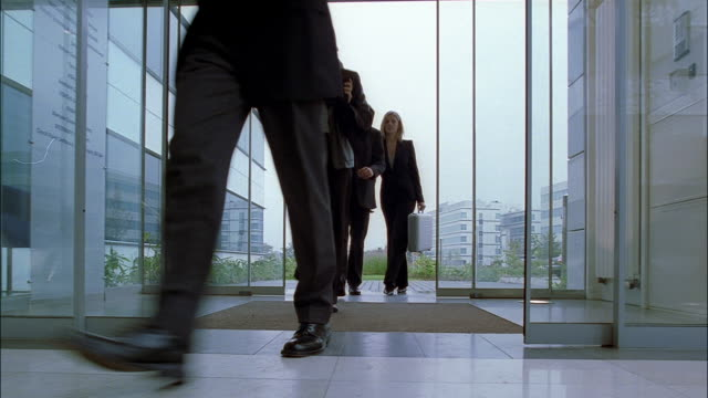 Four businessmen and a businesswoman enter a lobby of an office building.