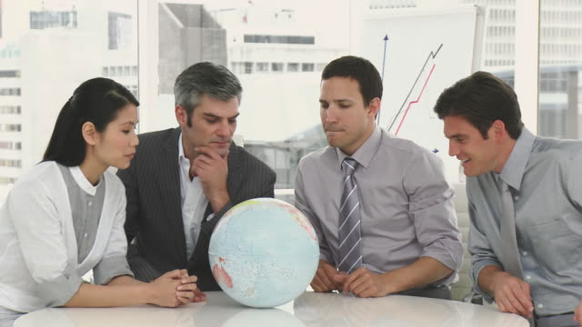 ms pan four businessmen having meeting in office, looking at globe / cape town, western cape, south africa - liniendiagramm stock-videos und b-roll-filmmaterial