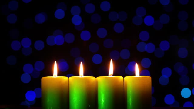 Four candles on blurred light background