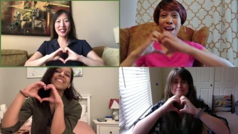 vídeos y material grabado en eventos de stock de four cheerful women chat on their webcams and make hearts at each other - vinculación