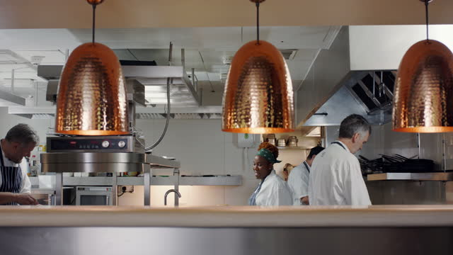 four chefs working in commercial kitchen - uniform stock videos & royalty-free footage