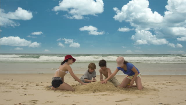 T/L, WS, Four children (12-13, 14-15) building sand castle on beach, Byron Bay, New South Wales, Australia