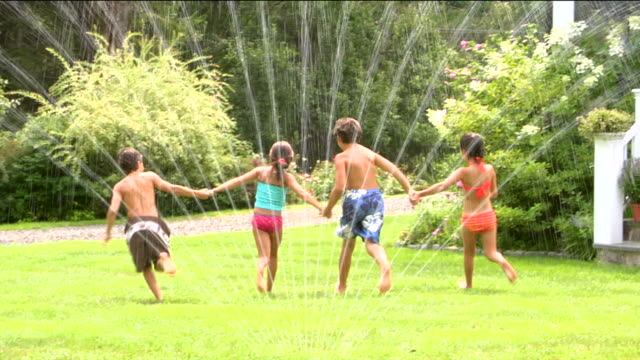 WS ZI MS Four children holding hands and running through sprinkler on lawn / Sherman, CT, USA