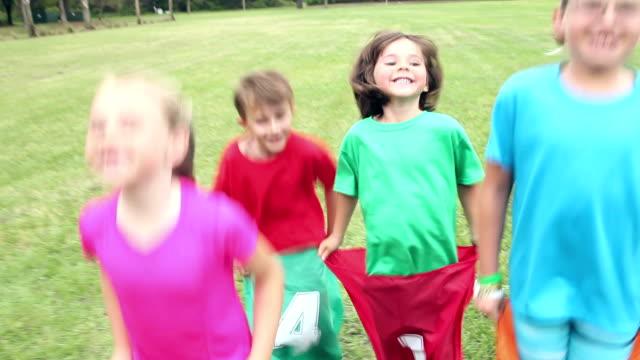 four children in park having potato sack race - sack race stock videos & royalty-free footage