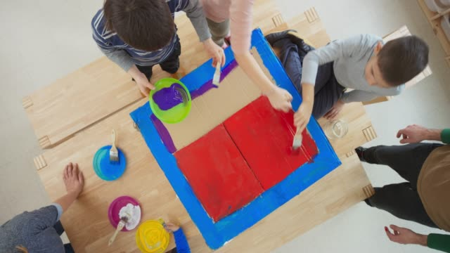 four children painting a carton box with red and blue paint - carton stock videos & royalty-free footage