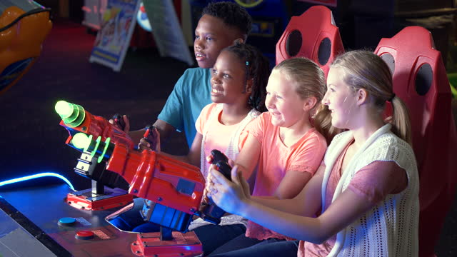 four children playing amusement arcade game - 14 15 years stock videos & royalty-free footage