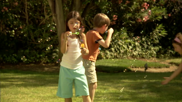 ms, pan, four children (4-5, 6-7) playing with bubbles in garden - sister stock videos & royalty-free footage