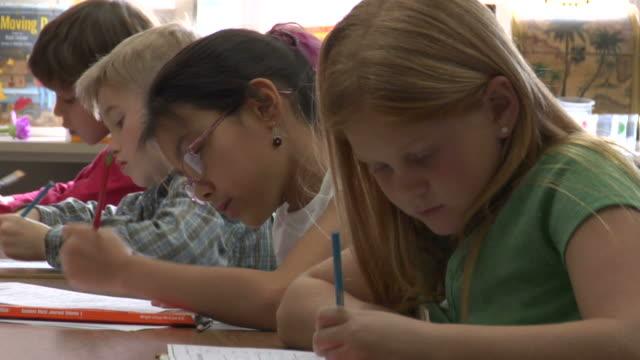 cu, four children (6-7, 8-9) raising hands in classroom - korta ärmar bildbanksvideor och videomaterial från bakom kulisserna
