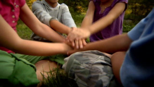 ms tu four children sitting in field and stacking their hands in teamwork sign before lifting them up toward the sky/ bovina, new york - stacking stock videos and b-roll footage