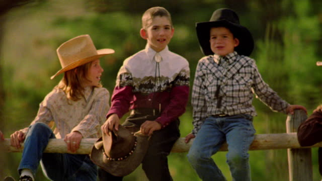 stockvideo's en b-roll-footage met portrait four children + teens in cowboy hats sitting on fence of corral talking + smiling / montana - cowboyhoed