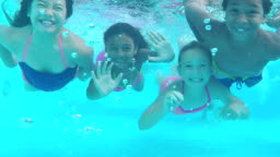 Four children underwater swimming toward camera