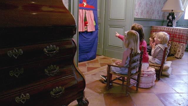 vídeos de stock e filmes b-roll de ms, ds, four children (2-3, 4-5, 8-9) watching puppet theater at home, saint ferme, gironde, france - fantoche