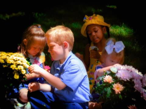 vídeos y material grabado en eventos de stock de four children with flowers. - encuadre de tres cuartos