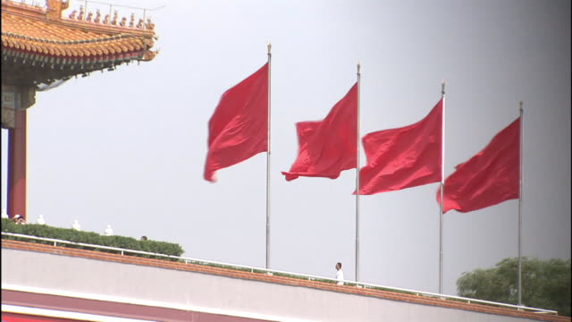 four chinese flags wave atop a building in beijing's forbidden city. - forbidden city stock videos & royalty-free footage