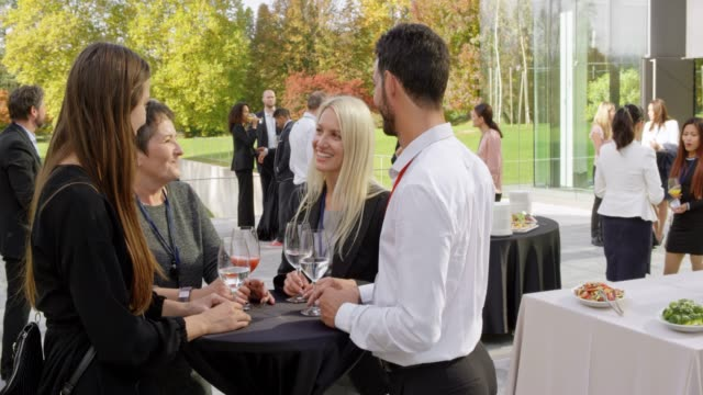 four colleagues attending a conference talking outside during a coffee break - business conference stock videos & royalty-free footage