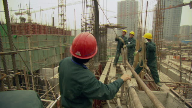 ms four construction workers moving tube that pours cement / shenzhen, guangdong, china - 工事点の映像素材/bロール