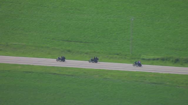 WS TS AERIAL POV Four couples riding on motorbikes in farmland / Iowa County, Iowa, United States