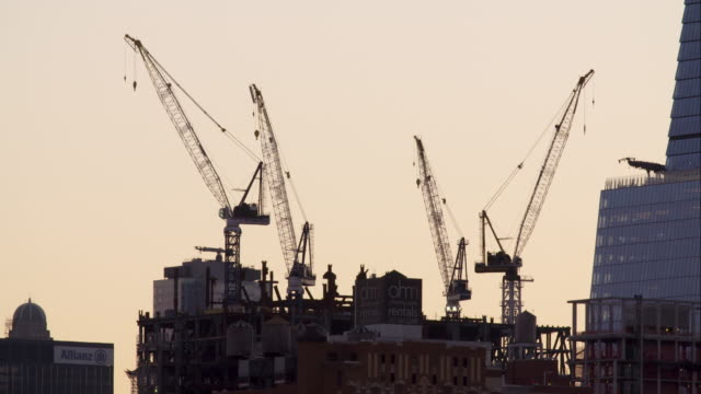 four cranes stand tall at new york city construction site - クレーン点の映像素材/bロール