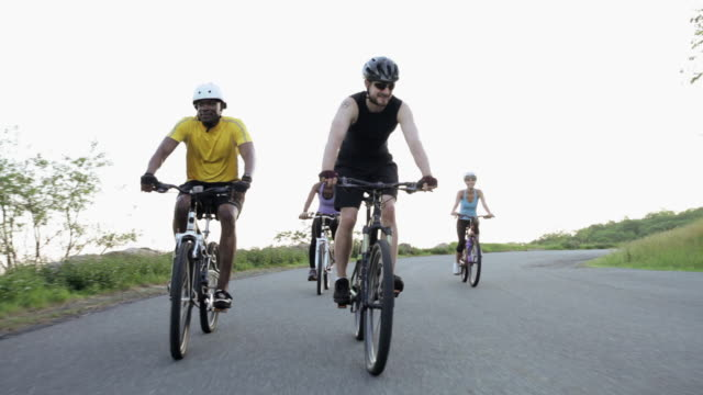 four cyclists riding along road - kleine personengruppe stock-videos und b-roll-filmmaterial
