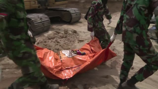 stockvideo's en b-roll-footage met four days after a tsunami hit the indonesian island of sulawesi bodies are being buried in a mass grave in the hills of palu - slachtoffer