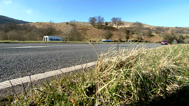 four dead in powys car crash; wales: powys: a470 near brecon: ext police notice appealing for information at roadside traffic along a470 past scene... - 中央ウェールズ点の映像素材/bロール