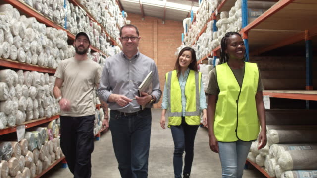 Four diverse team workers walking at aisle in warehouse