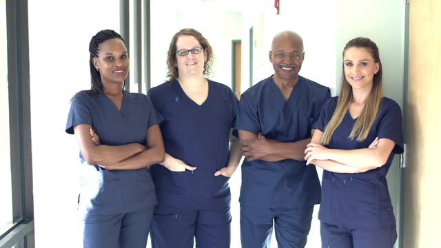 four doctors or nurses working in hospital - scrubs stock videos & royalty-free footage
