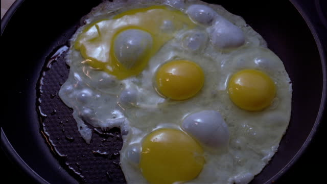 Four eggs fall into a hot frying pan and begin cooking.