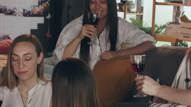 vídeos y material grabado en eventos de stock de cuatro amigas animando a la buena salud y la amistad con el vino tinto - amistad femenina