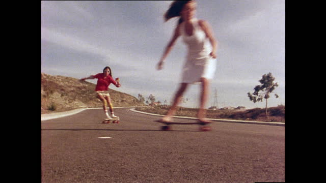 four female skateboarders skateboard past the camera including ellen o'neal at the front, and ellen berryman wearing no shoes and a skirt; 1978. - young women stock videos & royalty-free footage