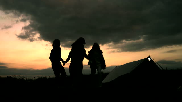 four friends dancing outside their tent at sunset silhouetted by the sky - tent stock videos & royalty-free footage